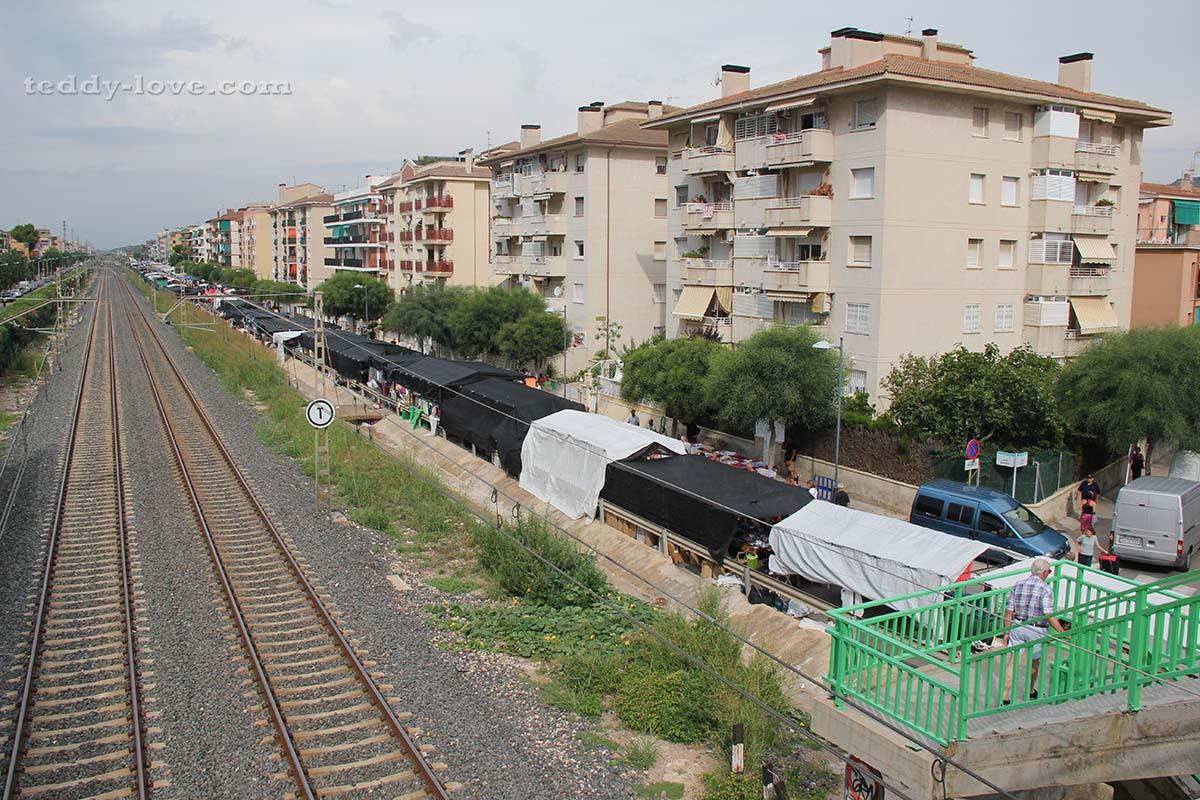 Пешеходный переход над железной дорогой, на другой стороне временный рынок.